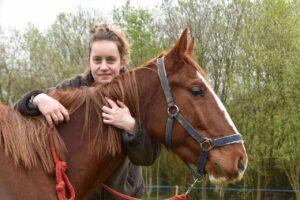 Lady cuddling a horse