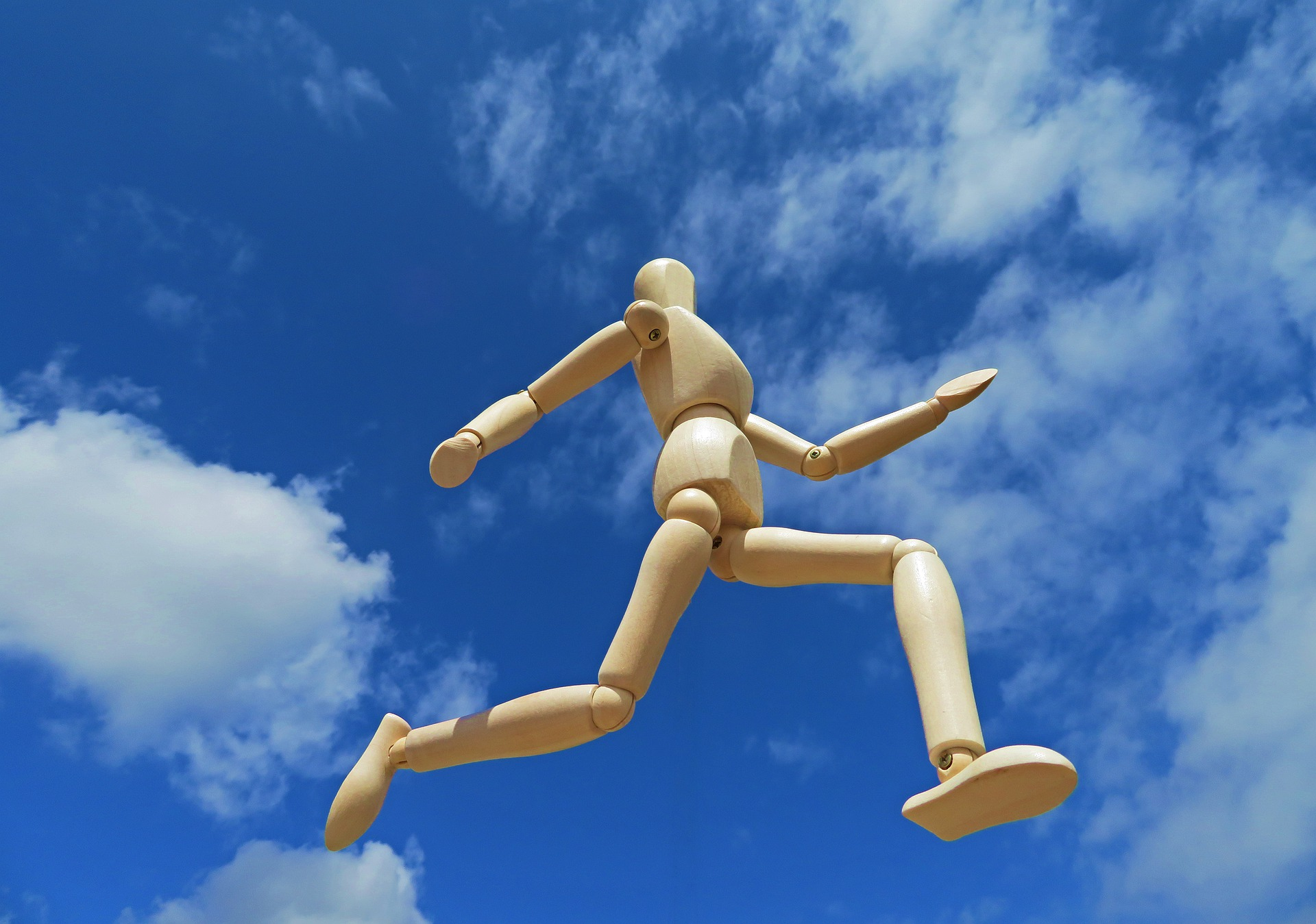 Reaching your potential - wooden doll walking in the air for personal development